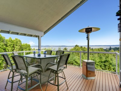 A beautiful outdoor deck with patio heater and outdoor furniture over the unobstructed view of wide lake
